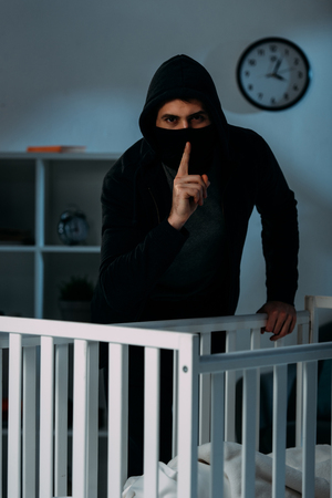 Kidnapper in mask standing near crib and showing hush sign