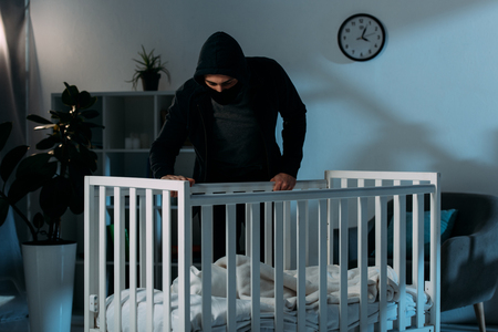 Kidnapper in black clothes standing in dark room and looking in crib