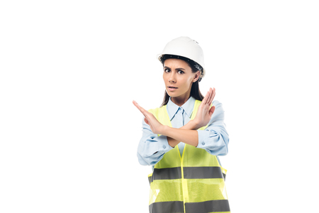 Worried engineer in hardhat showing stop sign isolated on white