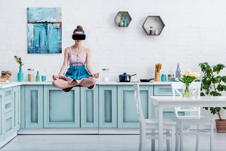 young woman levitating in air in lotus pose and in virtual reality headset Standard-Bild - 120138577