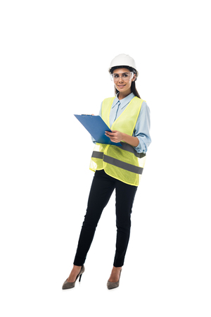Full length view of engineer in hardhat holding clipboard isolated on white Stock Photo