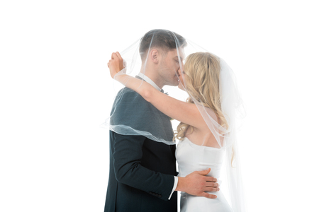 happy bride kissing bridegroom while covering him with bridal veil isolated on white