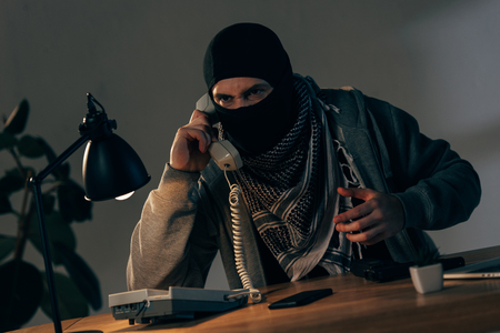 Aggressive terrorist in black mask sitting at table and talking on telephone
