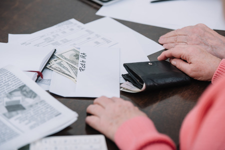 cropped view of senior couple sitting at table with paperwork, money and envelope with roth ira lettering