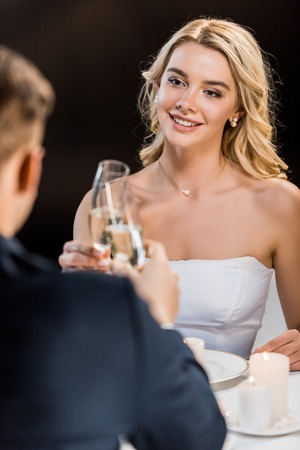 selective focus of young couple clinking glasses of champagne on black background Stock Photo