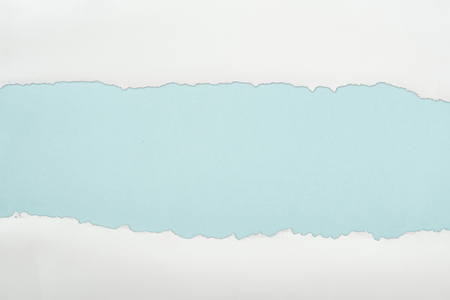 ripped white textured paper with copy space on light blue background