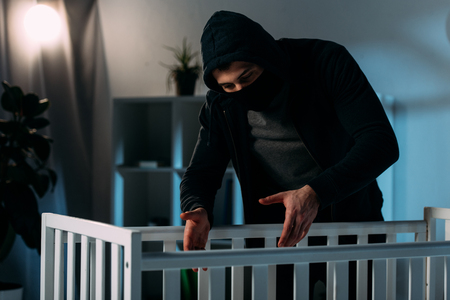 Criminal in mask and black clothes kidnapping child from crib Stock Photo