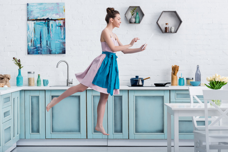 young happy barefoot woman levitating in air while using digital tablet in kitchen