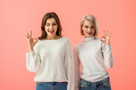 attractive brunette and blonde girls showing ok sign isolated on pink Stock fotó