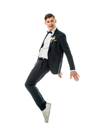 cheerful groom dancing in black suit and white sneakers isolated on white Stock Photo - 120138807