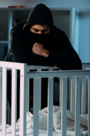 Pensive kidnapper in black clothes and mask looking in crib Stock Photo