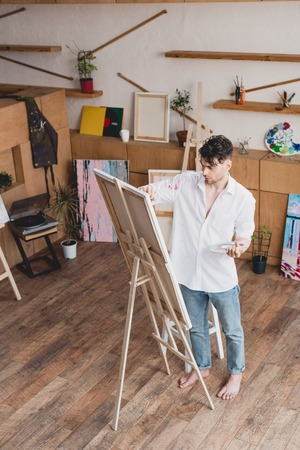 handsome artist in white shirt and blue jeans painting on canvas in painting studio