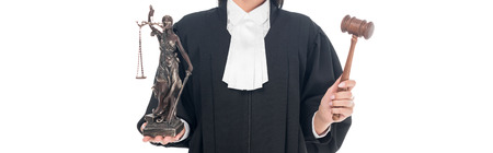 Panoramic shot of judge in judicial robe holding gavel and themis figurine isolated on white
