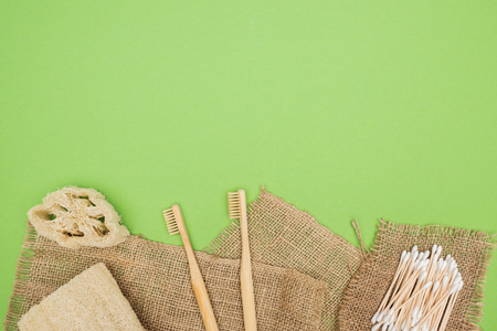 bamboo toothbrushes, organic loofah, cotton swabs and sackcloth on light green background