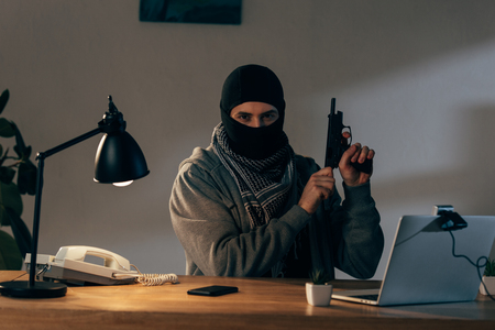 Criminal in black mask looking at camera and loading gun in room