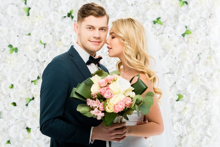 happy young bride and groom holding wedding bouquet on white floral background Stock Photo