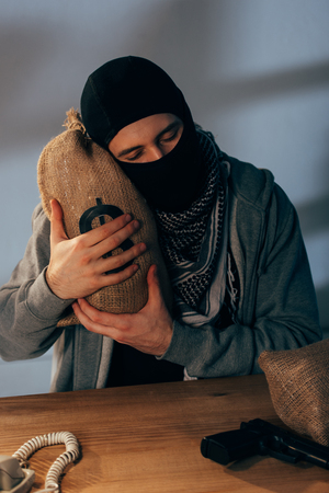 Pleased terrorist in mask embracing money bag with closed eyes Stock Photo