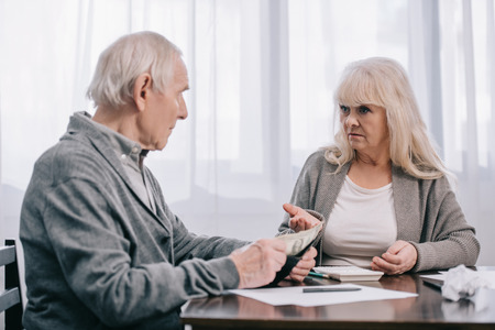 senior couple having discussion while sitting at table with paperwork