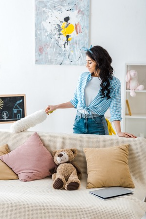 pretty african american woman cleaning sofa Stockfoto