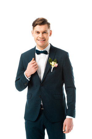 happy handsome bridegroom in black suit looking at camera isolated on white