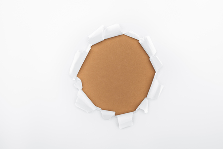ripped hole in white textured paper on brown background Reklamní fotografie