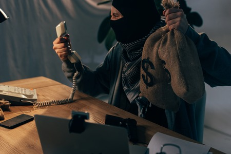 Angry terrorist in black mask holding money bags and looking at handset Stock Photo