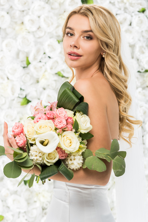 attractive young woman with wedding bouquet on white floral background