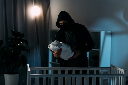 Kidnapper in mask and hoodie holding infant child while standing near crib
