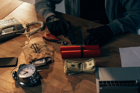 Partial view of terrorist in black gloves with dynamite, gun and dollar banknotes