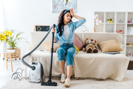 tired african american woman sitting on sofa while holding vacuum cleaner rod