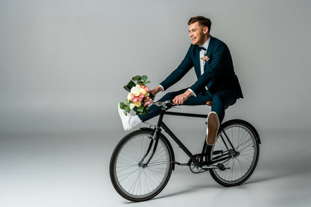 happy groom in elegant suit and sneakers riding bike and holding wedding bouquet on grey background Stock Photo