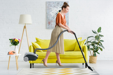side view of elegant young woman levitating in air while vacuuming carpet Stok Fotoğraf