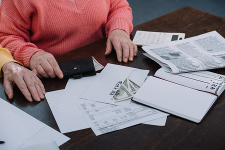 cropped view of senior couple sitting at table with paperwork, envelope with 'roth ira' lettering, money and notebook Stock Photo - 120139631