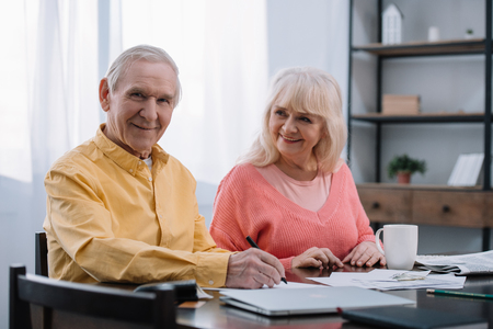 happy senior couple sitting at table and filling documents at home Stockfoto