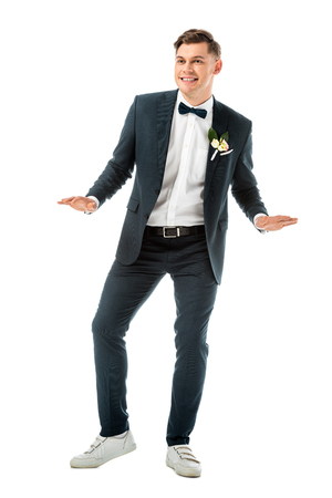 happy young groom dancing in black elegant suit and white sneakers isolated on white
