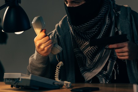 Partial view of angry criminal holding handset and aiming gun Stock Photo