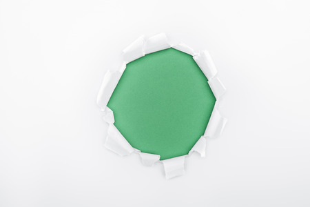 torn hole in white textured paper on green background