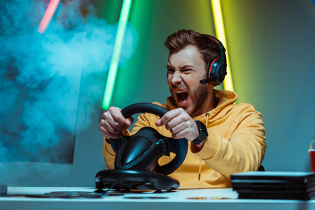 angry and handsome man in headphones playing video game with steering wheel