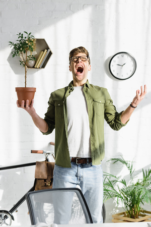 cunning handsome man in green shirt and jeans holding pot with plant in office Stock Photo