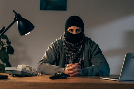 Terrorist in mask sitting at table with interlaced fingers