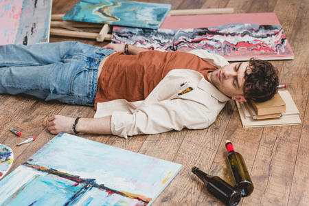 exhausted artist lying on wooden floor, surrounded with paintings, draw utensils and empty bottles