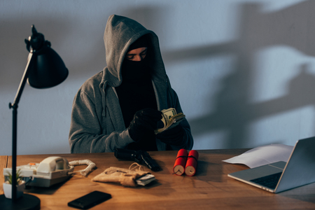 Terrorist sitting in room with weapon and counting dollar banknotes