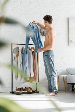 selective focus of man with bare torso standing near clothes rack and holding shirt in bedroom