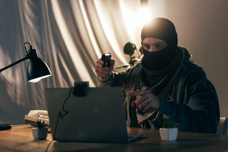 Criminal in mask pointing with finger and aiming gun at laptop screen Stock Photo