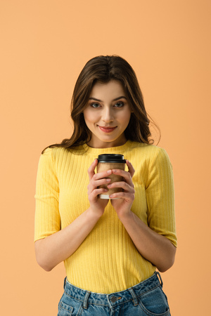 Front view of tricky brunette girl holding paper cup of coffee isolated on orange 스톡 콘텐츠