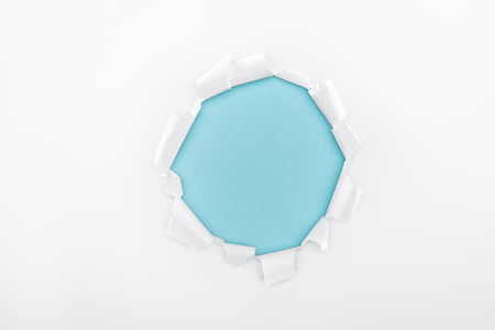 torn hole in textured white paper on blue background