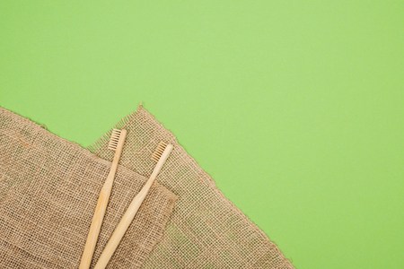bamboo toothbrushes and brown sackcloth on light green background