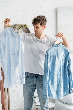 handsome man in white t-shirt holding shirts in bedroom