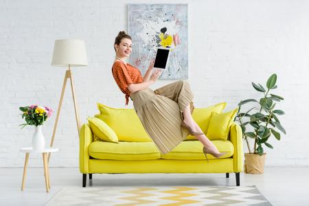 Elegante joven feliz levitando en el aire y mostrando tableta digital con pantalla en blanco en la sala de estar Foto de archivo