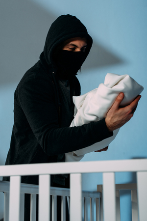 Kidnapper in mask standing beside crib and holding infant child Stock Photo